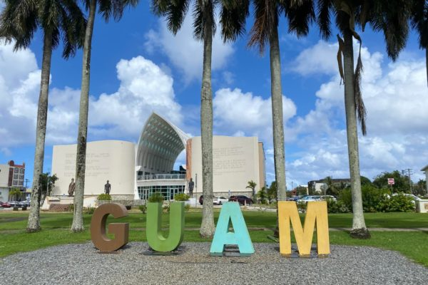 Sign that spells out Guam in a park under palm trees