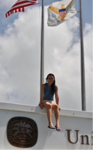 Tiffany Gonzalez sits atop a sign for the University of the Virgin Islands